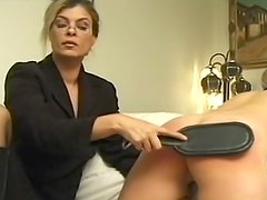 Glamorous and sexy doll with glasses is punishing her female slave's ass on the sofa