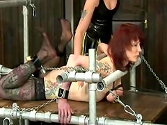Tattooed bondage sub in the dark dungeon