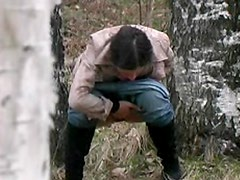 Girl in jeans pisses in the woods