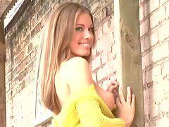 Tiffani Amber the lovely babe poses standing against the wall