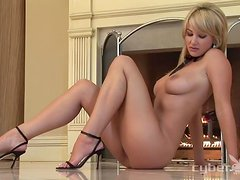 Hot blonde Kate Brenner poses for the cam near a fireplace