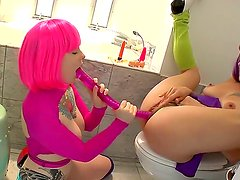 Tattooed freaks Belladonna and Misti Dawn testing their big dual-dildo in the toilet