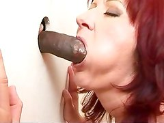 Mature redhead does her duty at a gloryhole
