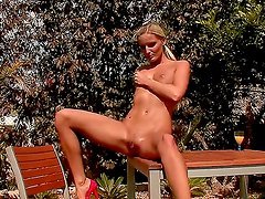 Beautiful tanned blonde Neilla work her pussy manually at the bench in the park