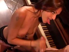 Hot slim chick sits on piano bench and gives handjob
