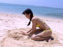 Slim and zesty Rei Toda rolling on the hot sand on the beach