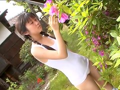 Asian student chick with dark hair walks in the garden in her swimming suit