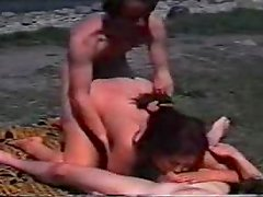 Brunette milf gets fucked by her hubby and his buddy on a beach