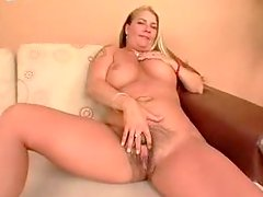 Bosomy blonde plays with her meaty hairy snatch and moans in pleasure
