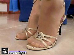 Sandy the cute blonde in high heels fingers her shaved pussy