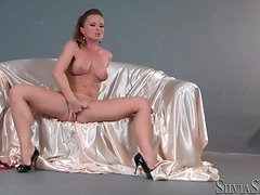 Solo pornstar on satin sheets rubs her pussy